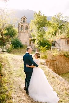Жених и невеста идут обниматься к древней колокольне возле церкви в прчане, вид сзади