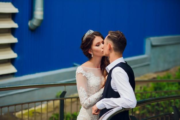Жених и невеста гуляя в город, день свадьбы, принципиальная схема замужества. жених и невеста в городской предпосылке. молодая пара собирается на лестнице в день свадьбы.