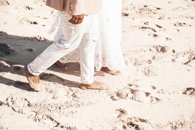 ビーチに沿って一緒に歩く新郎新婦。ロマンチックな結婚式のカップル