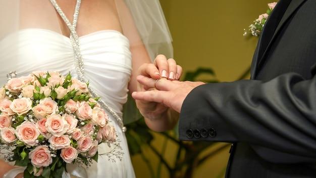신부와 신랑은 서로에게 결혼 반지를 끼고 있습니다. 사랑과 새로운 가족.