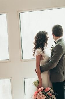 大きな光の窓の背面図のそばに立っている美しいウェディングブーケと新郎新婦