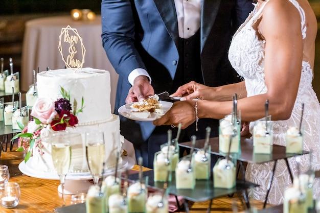美しい白いウエディングケーキを切る新郎新婦