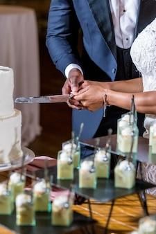신부와 신랑이 아름다운 하얀 웨딩 케이크를 절단