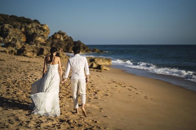 모래 해변에서 산책하는 신랑과 신부