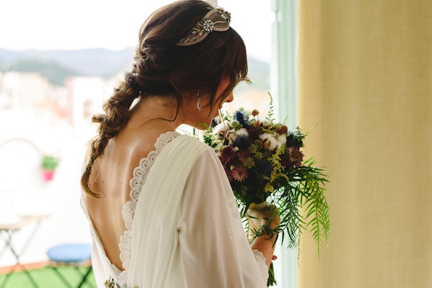 Bride back with her wedding dress holding her bouquet.
