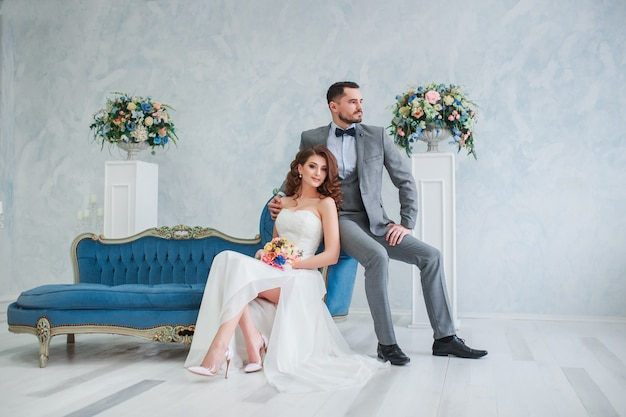 Bride in beautiful dress and groom in gray suit sitting on sofa indoors. trendy wedding style