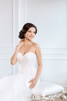 Bride in beautiful dress sitting on chair indoors in white studio interior like at home.