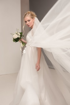 Bride in beautiful dress standing indoors in white studio interior like at home. trendy wedding style shot. young attractive caucasian model like a bride tender looking.