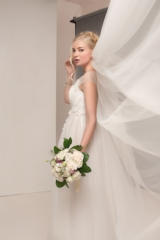 Bride in beautiful dress standing indoors in white studio interior like at home.