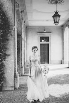 Bride in a beautiful dress with a bouquet of flowers stands in an arched corridor