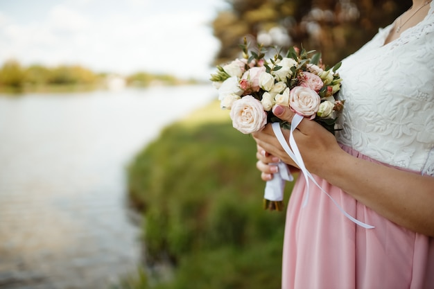 Bride in a beautiful dress with a train holding a bouquet of flowers and greenery