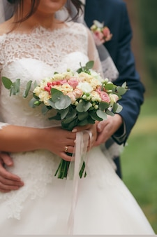 A bride in a beautiful dress with a train holding a bouquet of flowers and greenery