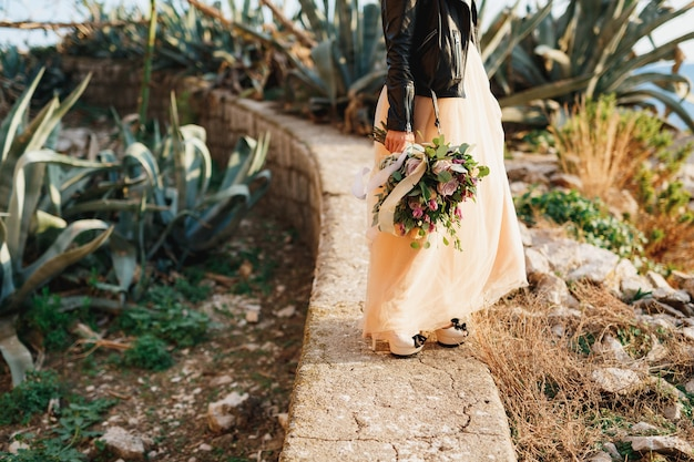 Bride in a beautiful pastel dress and a leather jacket stands on a path with a bouquet of flowers