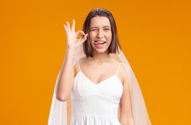Bride in beautiful wedding dress  happy and joyful sticking out tongue showing ok sign standing over orange wall