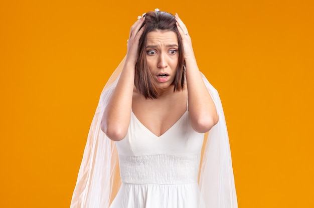 Bride in beautiful wedding dress looking aside being shocked with hands on her head