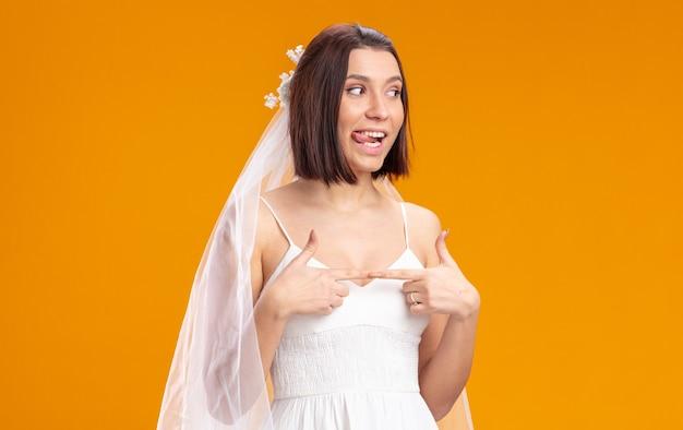 Sposa in un bellissimo abito da sposa che guarda da parte felice e gioiosa che tira fuori la lingua