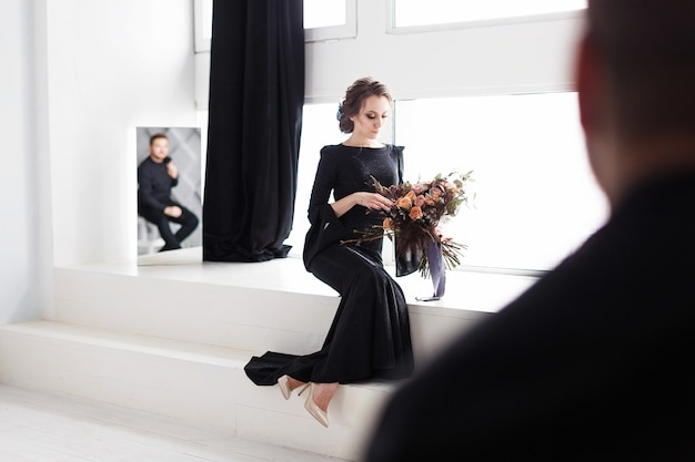 The bride in black dress. reflecting in the mirror. white studio room with windows.