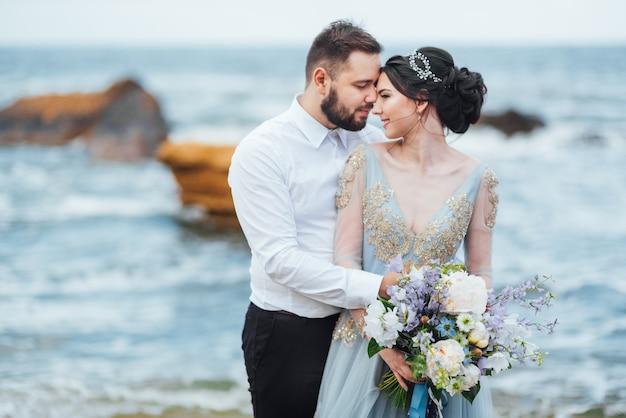 Bride in a blue dress walk along the ocean shore