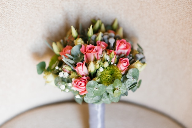 Bride bouquet of eucalyptus leaves, roses and eustom on beige background. accessory for the bride at the wedding