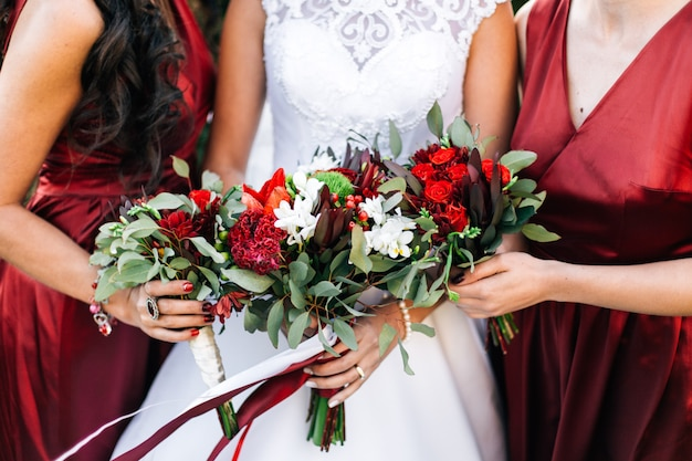 Bride and bridesmaid are holding bouquets of flowers in hands