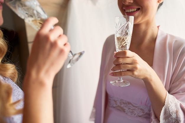 Bride and bridesmaids drink champagne preparing in the morning