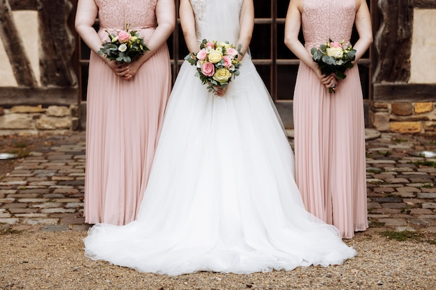 The bride and bridesmaids in an elegant dress is standing and holding hand bouquets of pastel flowers