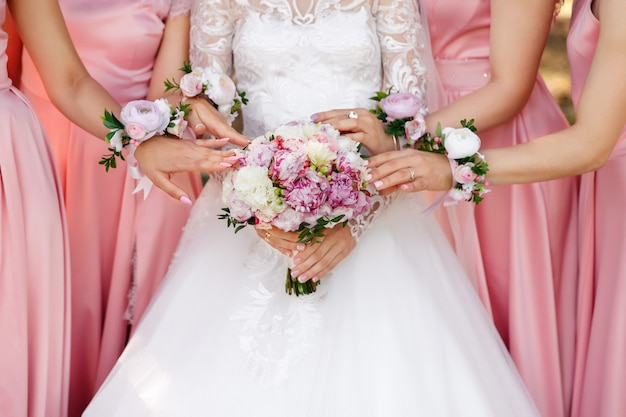 Bride and bridesmaids holding wedding bouquet