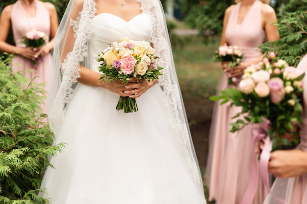 Bride and bridesmaids in pink dresses posing with bouquets at wedding day.