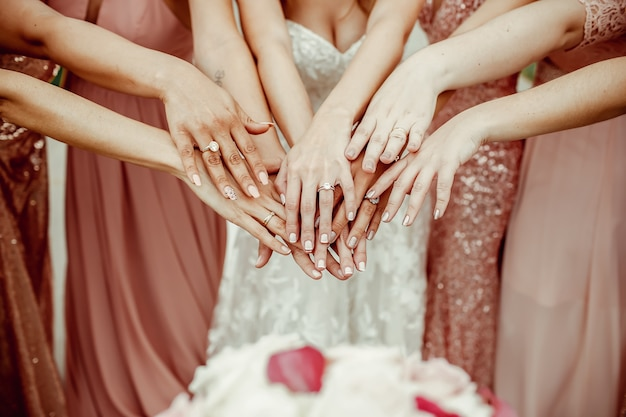 Bride and bridesmaids in pink dresses rich out their hands with