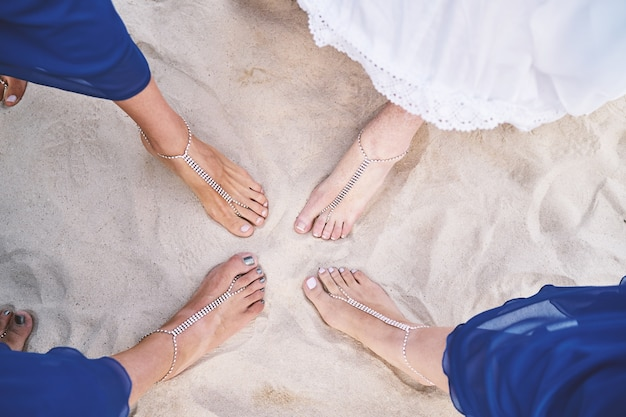 Bride and bridesmaids show feet with bracelets on the sand