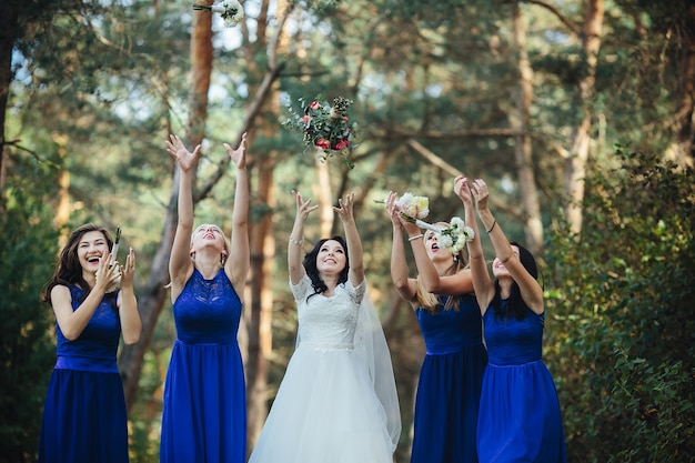 Bride and bridesmaids throwing up bouquets