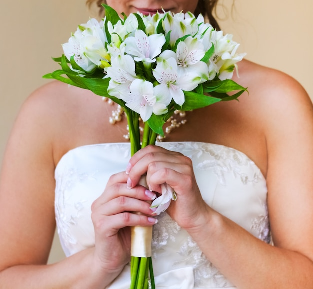 The bride brings to her face a delicate wedding bouquet of white alstromeria