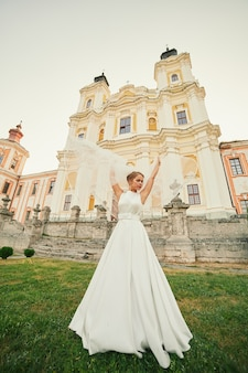 The bride in a chic dress is whirling near the church