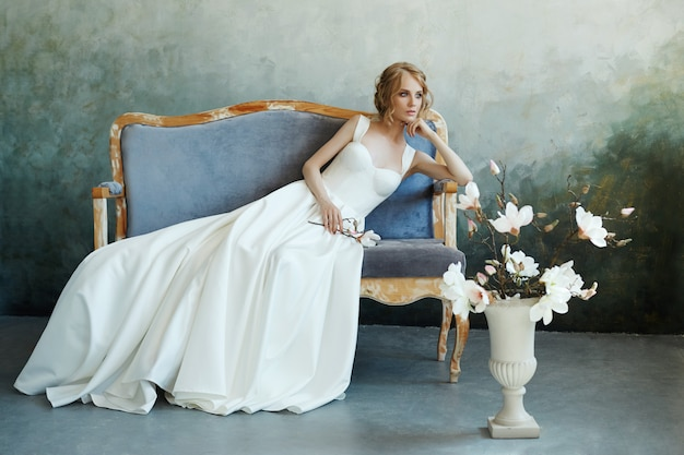 Bride in a chic long dress lying on the sofa couch. white wedding dress