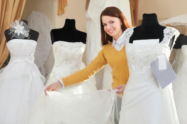 Невеста выбирает свадебное платье в свадебном бутике