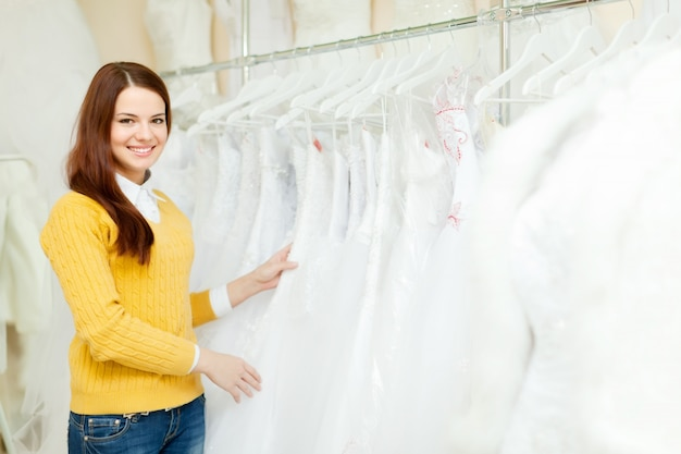 Bride chooses wedding outfit at shop