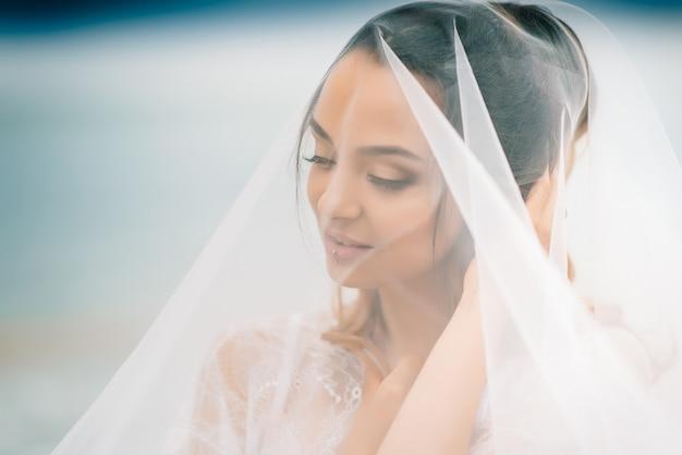 Крупным планом невесты под вуалью на фоне голубого неба и черного моря