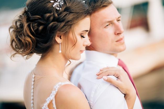 Bride closing her eyes hugs the groom from behind closeup