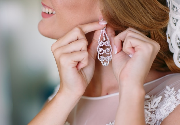 The bride corrects the earring, beautiful earrings and hands of the bride
