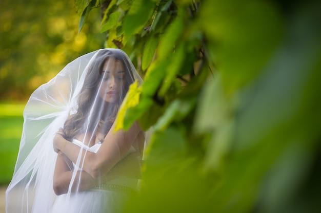 «невеста покрыта завесой, стоящей на зелени» Бесплатные Фотографии