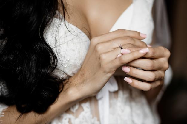 花嫁は美しいマニキュアと最小限の婚約指輪を示しています