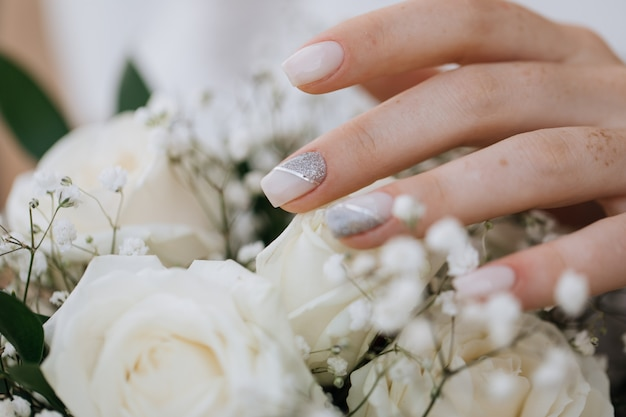 Bride demonstrates her manicure over wedding bouquet