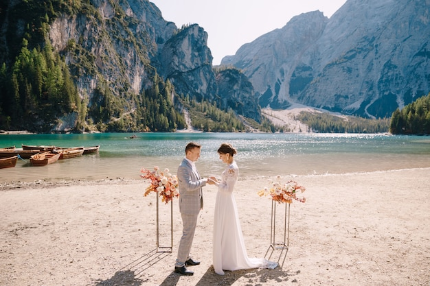 The bride dons a ring to the groom at the venue for the ceremony, with an arch of autumn floral columns, against the backdrop of lago di braies in italy