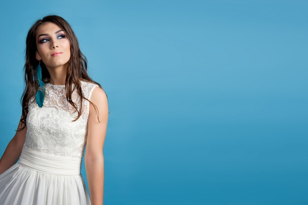 Bride dreaming, blue background. brunette young pretty woman in white dress is dreaming. desire. copy space