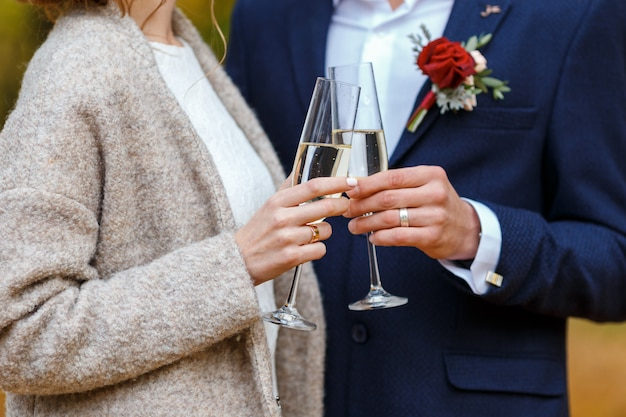 Bride in dress and coat and groom in blue suit hold in their hands wineglasses with champagne