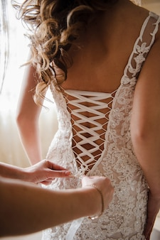 Bride in a dress. view from the back. lacing. mom or sister lace dress on the bride.