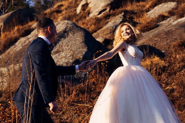 The bride in a dress with lace holds the grooms hand and they walk