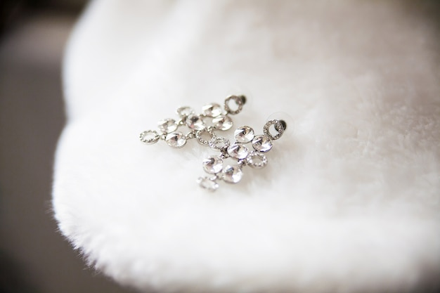 Bride earrings lie on white cape closeup