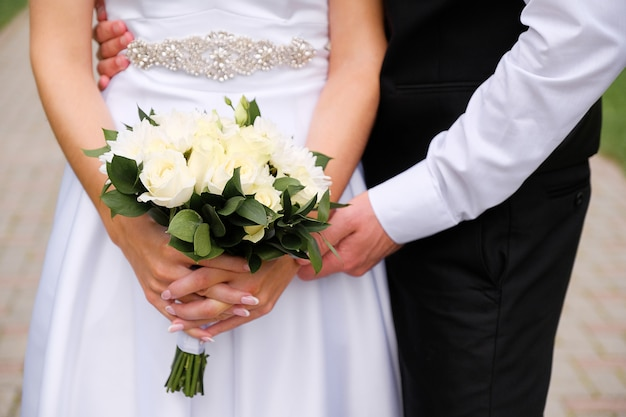 The bride in an elegant wedding dress is holding a beautiful bouquet of white roses and chrysanthemums and green leaves. embrace the newlyweds, the hands of the bride and groom close-up, outdoors.