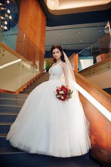 Bride in elegant wedding dress standing on stairs